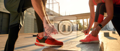 Fototapete Active morning. Close up photo of two people in sport clothes tying shoelaces before running together outdoors