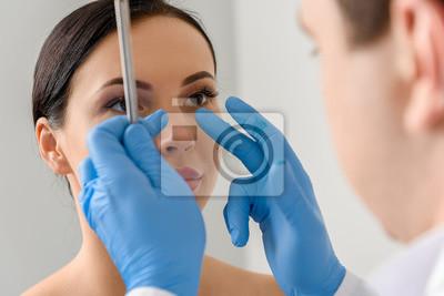 Fototapete Arzt untersucht Gesicht der heiteren Frau