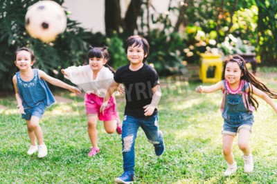 Fototapete Asian and mixed race happy young kids running playing football together in garden. Multi-ethnic children group, outdoor sport exercising, leisure game activity, or childhood fun lifestyle concept