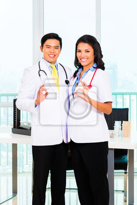 Asian Male And Female Doctor Standing Proud In His Office
