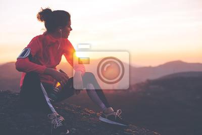 Fototapete Athletische Frau ruht nach einem harten Training in den Bergen bei Sonnenuntergang. Sport enge Kleidung.