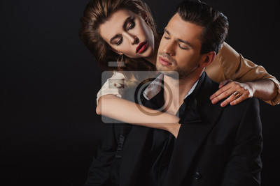 Fototapete attractive woman hugging handsome man in suit isolated on black