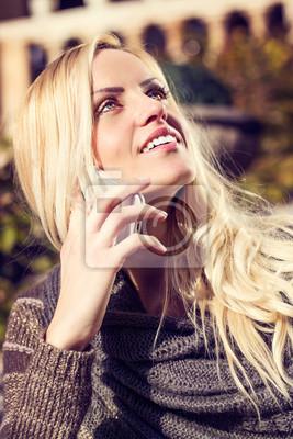 Attraktive blonde Frau im Chat auf ihrem Handy