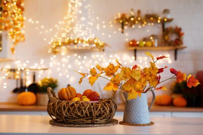 Fototapete Autumn kitchen interior. Red and yellow leaves and flowers in the vase and pumpkin on light background
