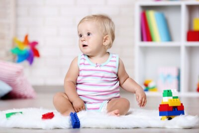 Fototapete Baby girl sitting on white carpet with toys