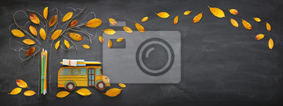 Fototapete Back to school concept. Top view banner of school bus and pencils next to tree sketch with autumn dry leaves over classroom blackboard background.