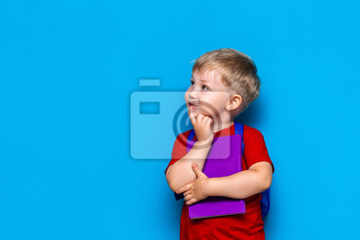 Fototapete Back to school Portrait of happy surprised kid in glasses isolated on blue background with copy space. new school knowledges