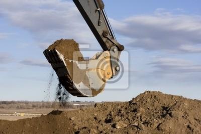 Baggerarm und Schaufel graben Schmutz auf der Baustelle