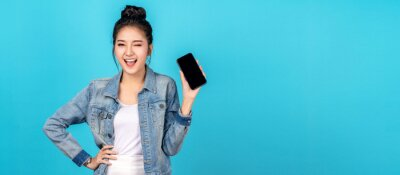 Fototapete Banner of asian woman feeling happiness, blinks eyes and standing hold smartphone on blue background. Cute asia girl smiling wearing casual jeans shirt and connect internet shopping online and present