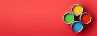 Fototapete Banner with four cans of colorful paint on red background. Top view on green, yellow, red and blue paints.