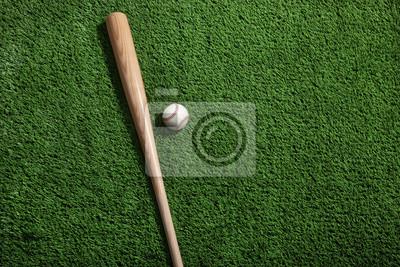 Baseball und Schläger auf grünem Rasen von oben betrachtet