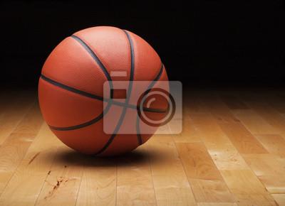 Basketball mit dunklem Hintergrund auf einer Holz-Turnhalle Boden