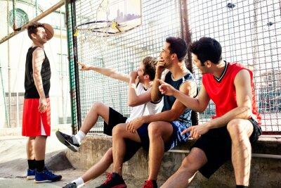 Basketball-Spieler eine Pause sitzt auf einer niedrigen Mauer