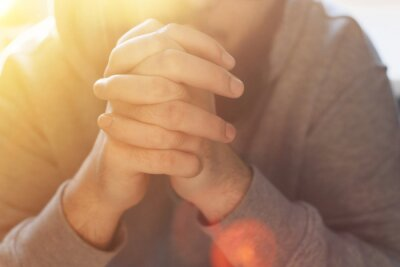 Fototapete Bearded adult man praying to God sitting at home in the sunbeam. A Muslim or Christian raises his hands to God. Crossed hands in prayer gesture close up