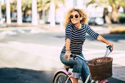 Fototapete Beautiful and cheerful adult young woman enjoy bike ride in sunny urban outdoor leisure activity in the city - happy people portrait - trendy female outside having fun