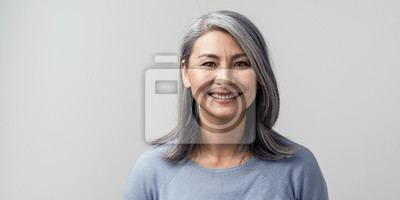 Fototapete Beautiful asian with grey hair smiling standing near the wall