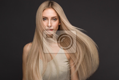 Fototapete Beautiful blond girl in move with a perfectly smooth hair, and classic make-up. Beauty face.