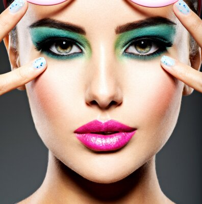 Fototapete Beautiful Face of a woman with green vivid make-up of eyes