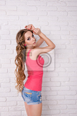 Fototapete beautiful girl with wavy long hair standing on white background