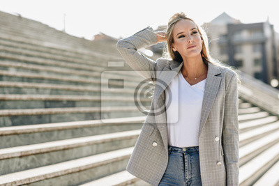 Fototapete Beautiful young blonde woman in urban background.