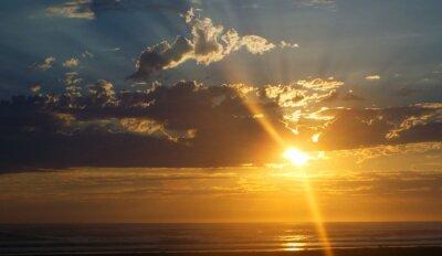 Fototapete Bewölkt Sonnenuntergang über dem Ozean mit Sonnenstrahlen in den Himmel