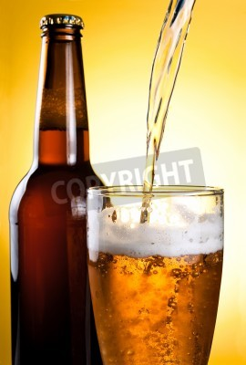 Fototapete Bier wird in Glas gegossen und Flasche auf gelbem Hintergrund