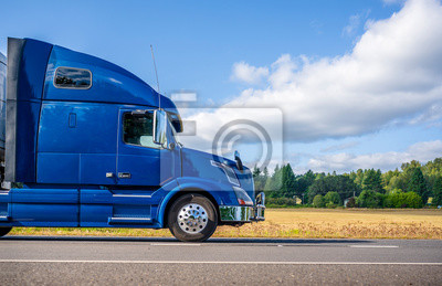 Fototapete Big rig blue semi truck transporting cargo in semi trailer driving on the flat road with yellow field