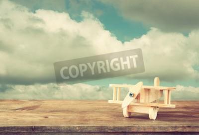 Fototapete Bild von Holz Spielzeug Flugzeug über Holztisch gegen bewölkten Himmel. Retro-Stil Bild