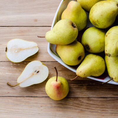 Fototapete Birnen in einer Schale und Birne Hälften auf einem hölzernen Hintergrund