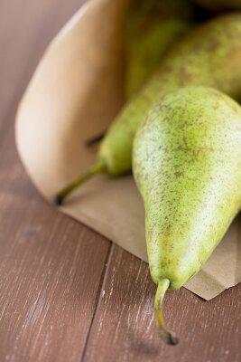 Fototapete Birnen von einer Obsttüte auf einem Holzbrett