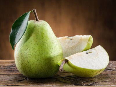 Fototapete Birnenfrucht mit Blatt auf hölzernem Hintergrund.