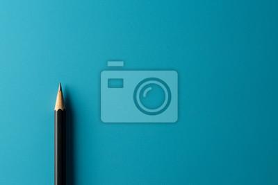 Fototapete Black pencil on blue paper background. - Business concept.