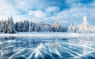 Fototapete Blaues Eis und Risse auf der Oberfläche des Eises. Gefrorener See unter einem blauen Himmel im Winter. Die Hügel von Pinien. Winter. Karpaten, Ukraine, Europa.
