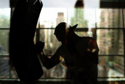 Fototapete Boxer trifft einen Boxsack gegen das Fenster, Schulung