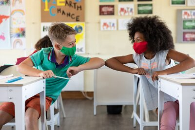 Fototapete Boy and Girl wearing face masks greeting each other by touching elbows at school