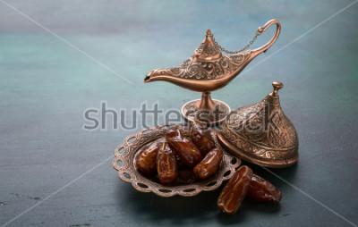 Fototapete Bronzeteller mit Daten und Aladdinlampe auf dunkelgrünem hölzernem Hintergrund. Ramadan Hintergrund. Ramadan Kareem.