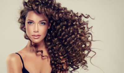 Fototapete Brunette Mädchen mit langen und glänzenden lockigen Haaren. Schönes Modell mit welliger Frisur.