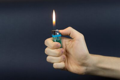 Fototapete Burning gas lighter in a human hand on a gray background.