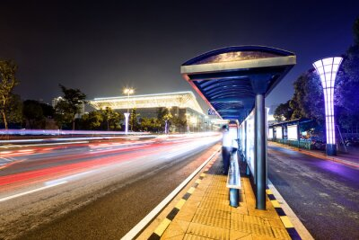 Fototapete bus station next to a road at night