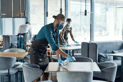 Fototapete Busy young male waiters in protective workwear cleaning tables in restaurant