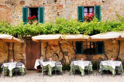 Fototapete Cafe Tische und Stühle außerhalb eines Gebäude aus Stein in der Toskana