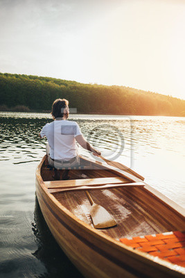 Fototapete Canoeist paddling the wooden boat