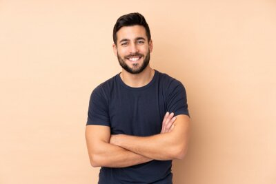 Fototapete Caucasian handsome man isolated on beige background keeping the arms crossed in frontal position