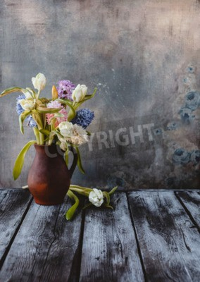 Fototapete Ceramic jug with spring flowers on wooden table