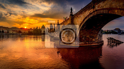 Fototapete Charles bridge (Karluv most) at sunrise, scenic view of the Old town with Old Town Bridge Tower, colorful sky and historic medieval architecture, Prague, Czech Republic. Holidays in Prague