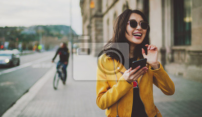 Fototapete Cheerful asian student girl wearing modern sunglasses laughing at friends' photos in social media by a mobile phone. Happy model look woman in casual outfit checking blog comments via smartphone.