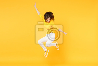 Fototapete Cheerful funny young woman in summer casual clothes jumping and spreading hands isolated on yellow orange wall background in studio. People sincere emotions, lifestyle concept. Mock up copy space.