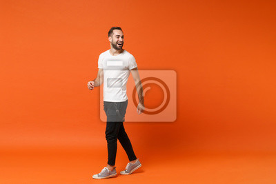 Fototapete Cheerful laughing young man in casual white t-shirt posing isolated on bright orange wall background studio portrait. People sincere emotions lifestyle concept. Mock up copy space. Looking aside.