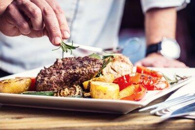 Fototapete Chef im Hotel oder Restaurant Küche nur Hände kochen. Vorbereitetes Rindersteak mit Gemüsedekoration.