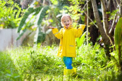 Fototapete Child playing in the rain on sunny autumn day. Kid under heavy shower with yellow duck umbrella. Little boy with duckling waterproof shoes. Rubber wellies boots. Fall outdoor activity by rainy weather